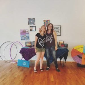 Erica Pugh and Crystal Ferrara standing in front of their art show table